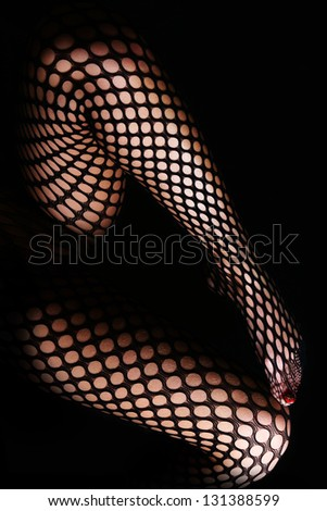 Woman long legs in pantyhose isolated on black