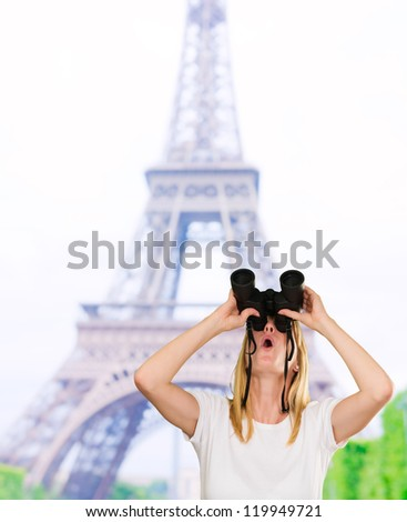 woman lookin up using binoculars in front of the eiffel tower - stock photo