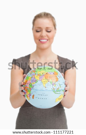 Woman looking a globe against white background - stock photo