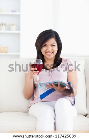 Woman looking ahead as she reads a magazine and holds a glass of red wine in a living room - stock photo