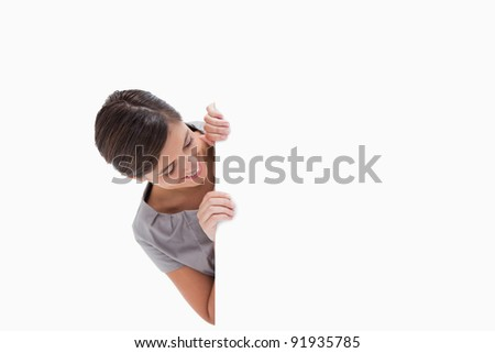 Woman looking around the corner against a white background - stock photo