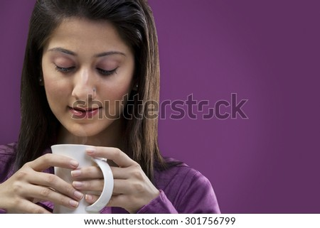 Woman looking at a cup of coffee