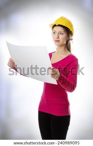 woman looking at a large sheet of paper wearing a hard hat - stock photo