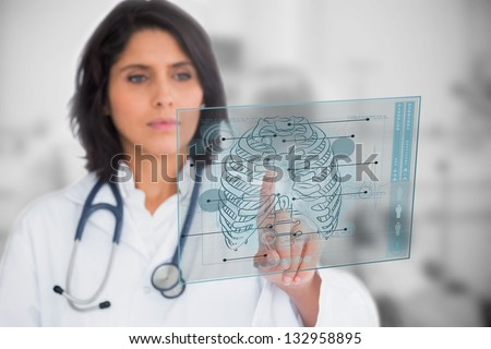Woman looking at a medical interface in the hospital - stock photo