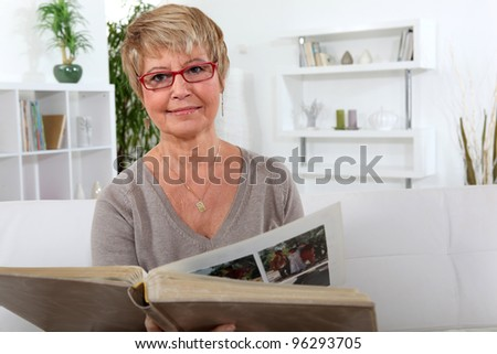 Woman looking at a photo album - stock photo