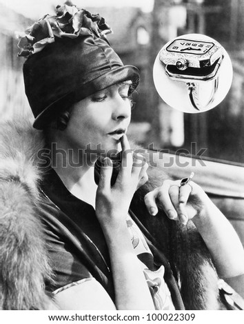 Woman looking at a watch ring - stock photo
