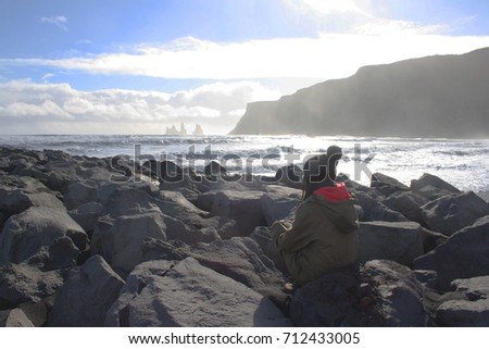 Woman looking at an icelandic shore landscape
