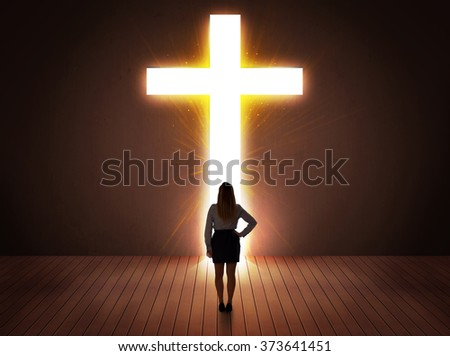 Woman looking at bright cross sign concept - stock photo