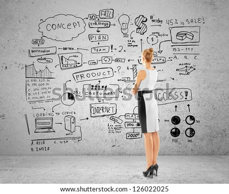 woman looking at business concept on brick wall - stock photo