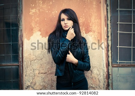 woman looking at camera and holding her collar. Specially toned photo - stock photo