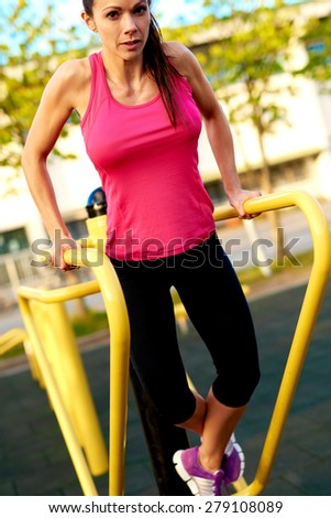 Woman looking at camera doing tricep dips outside on a dip stand with ankles crossed. - stock photo