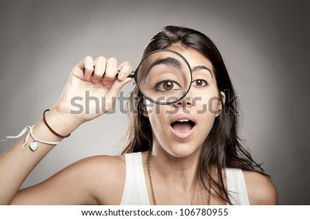 woman looking at camera through magnifying glass - stock photo