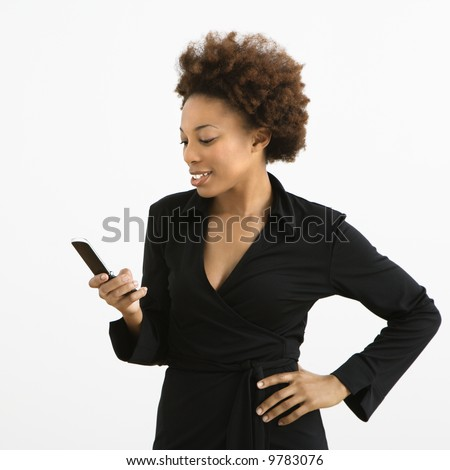 Woman looking at cellphone standing against white background.