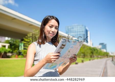 Woman looking at city map in Hong Kong - stock photo