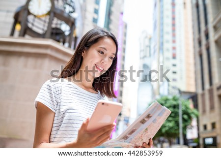 Woman looking at city map with mobile phone in Hong Kong city