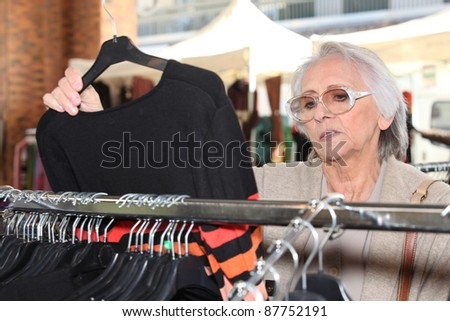 Woman looking at clothes on a rail - stock photo