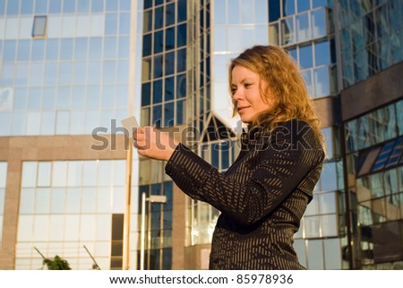 Woman looking at credit card, or doing shopping and paying opposite office building