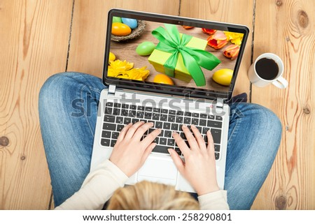 woman looking at easter still life on laptop - stock photo
