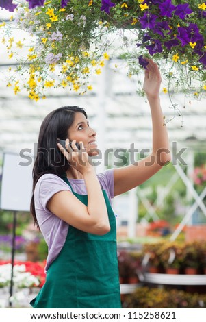 Woman looking at flowers in hanging basket working in garden center and phoning - stock photo