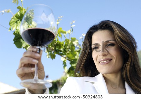 Woman looking at glass o red wine - stock photo