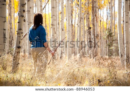 Woman Looking At Golden Autumn Leaves Through Forest of Aspen Trees - stock photo