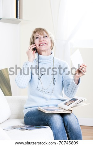 Woman looking at her grandson photographs - stock photo