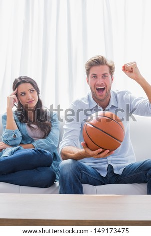 Woman looking at her husband cheering the basketball game at home on couch - stock photo