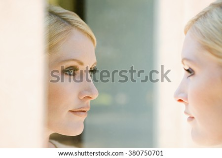 Woman looking at her reflection - stock photo