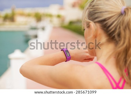 Woman looking at her smartwatch during workout - stock photo