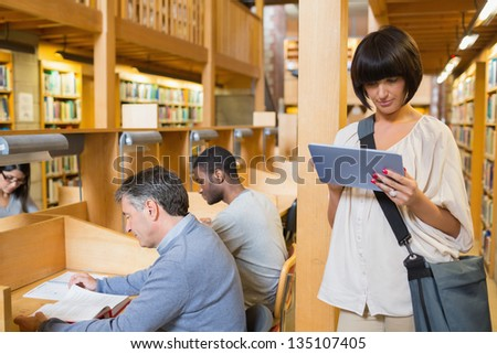 Woman looking at her tablet pc while other people are reading in the library - stock photo
