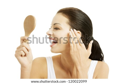 Woman looking at herself in the mirror , isolated on white - stock photo