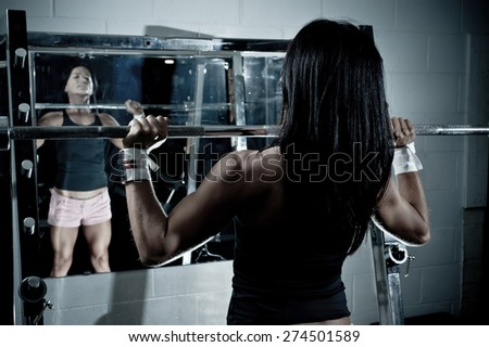Woman looking at herself in the mirror with weights in the gym - stock photo