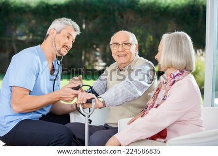 Woman looking at male doctor measuring blood pressure of senior man at nursing home - stock photo