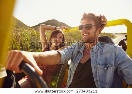 Woman looking at man driving car on a summer day. Loving young couple on road trip. - stock photo