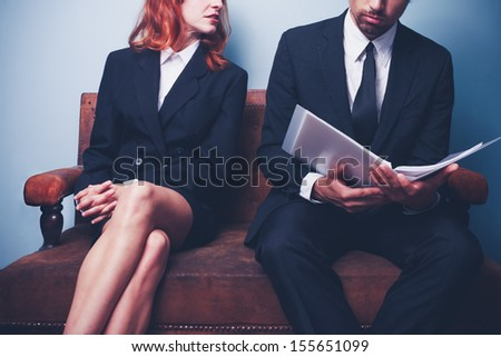 Woman looking at man reading company report - stock photo