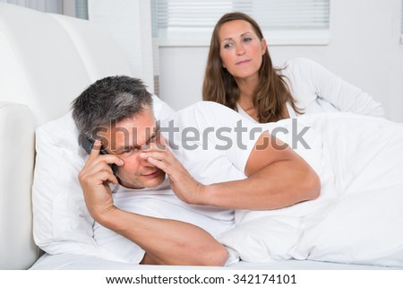 Woman Looking At Man Talking On Mobile Phone In Bedroom