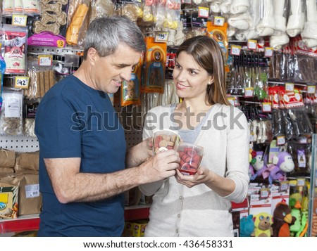 Woman Looking At Man While Choosing Pet Food In Store - stock photo