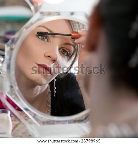 woman looking at mirror and applying make-up - stock photo