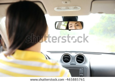 Woman looking at mirror in a car
