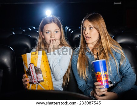 Woman looking at scared daughter watching movie in cinema theater - stock photo