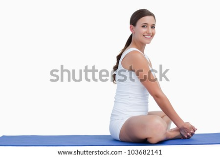 Woman looking at the camera while sitting on a mat against a white background