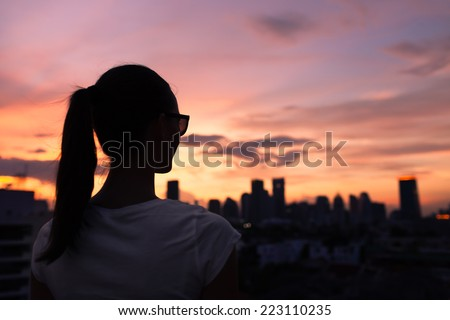 Woman looking at the city - stock photo
