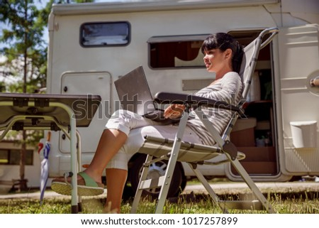 Woman looking at the laptop near the camping . Caravan car Vacation. Family vacation travel, holiday trip in motorhome RV. Wi-fi connection information communication technology.