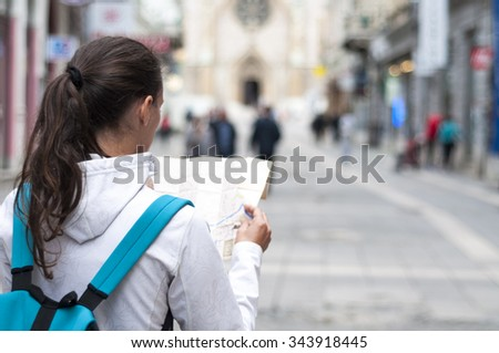 Woman looking at the map on the city street - stock photo