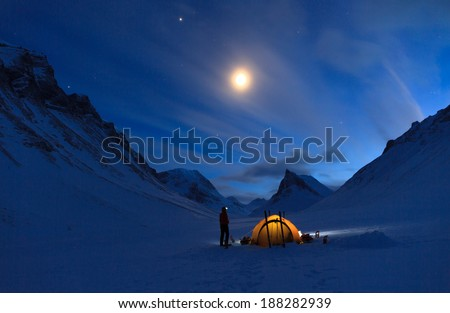 Woman looking at the night sky while camping in the snow covered mountains in Swedish Lapland (Nallo). - stock photo