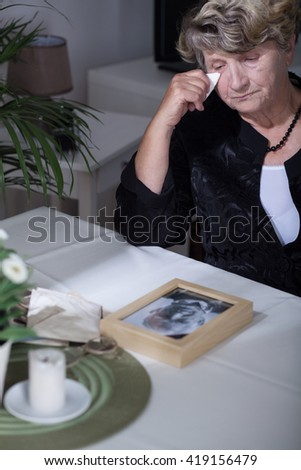 Woman looking at the photo of her dead husband - stock photo