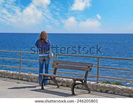 woman looking at the sea in autumn. Shot in Sardinia, Italy - stock photo