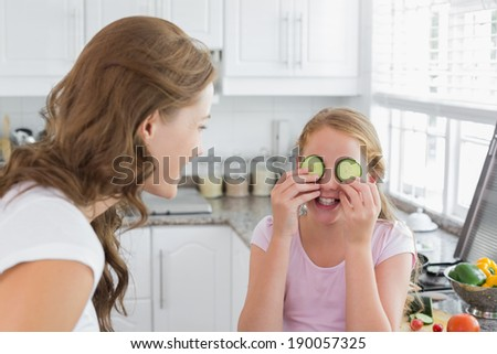 Woman looking at young girl keep cucumber slices on eyes in the kitchen at home