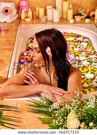 Woman looking away relaxing at water spa. A lot of flowers in  bathroom. - stock photo