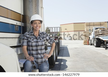 Woman looking away while standing by flatbed truck in timber yard - stock photo